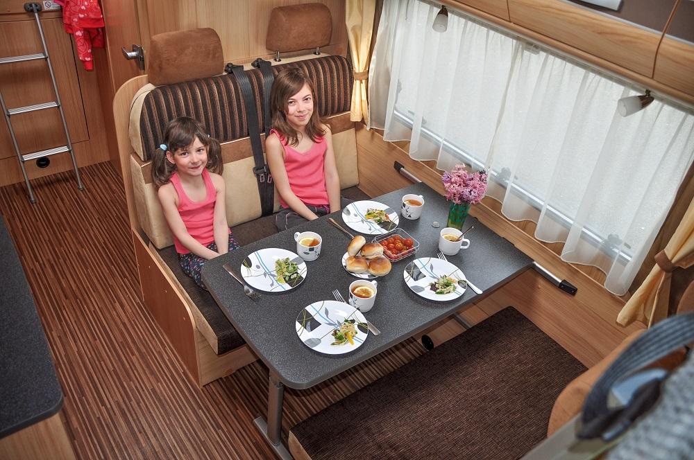dzieci siedzące przy stole w kamperze